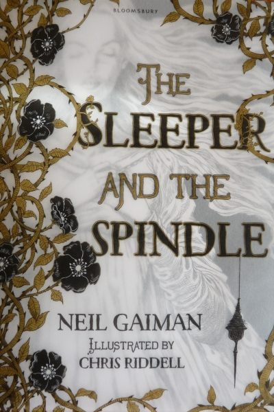 This is the cover of my personal copy of The Sleeper and the Spindle. The princess is ghostly behind a illuminated, misty rose and thorn jacket.